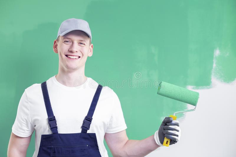 Upper body portrait of a young, smiling home renovation worker p. Osing with a paint roller on an unfinished, neo mint green wall background royalty free stock photo