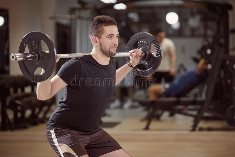 Upper body shot, squat exercise, young man holding barbell with weights on back shoulders. Unrecognizable people behind in gym out of focus royalty free stock photos