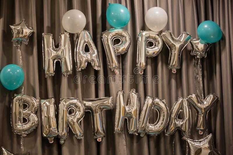 Upper case letters HAPPY BIRTHDAY from silver balloons view stock photography