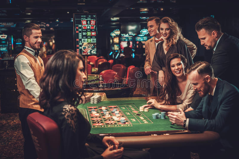 Upper class friends gambling in a casino stock image