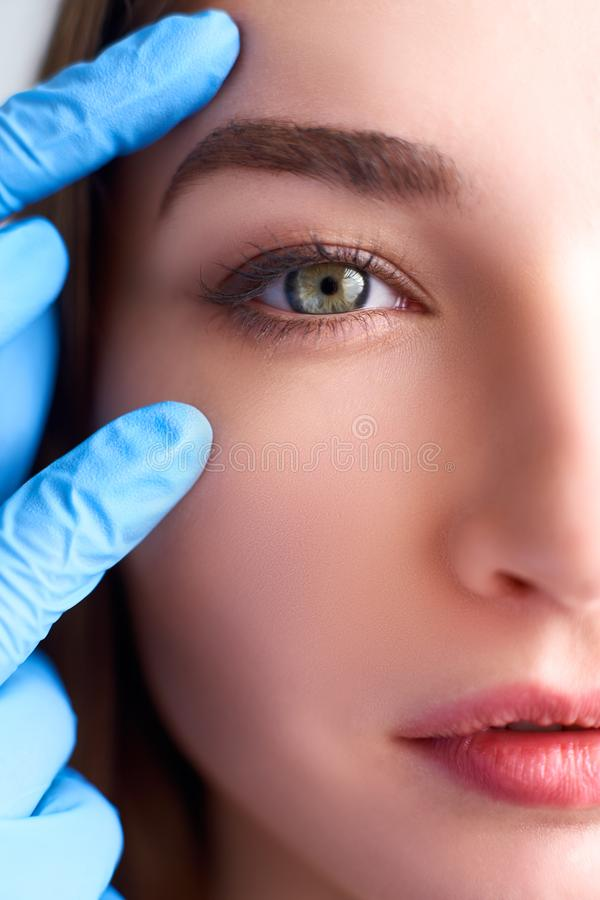 Upper eyelid reduction, double eye lid removal plastic surgery concept. Beautician doctor hands in gloves touching. Beautician doctor hands in gloves touching stock image