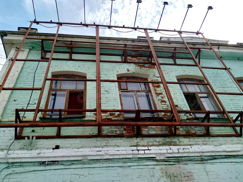 Upper floor the old brick building is painted with soft green paint. Window frames are wooden. Made of iron construction on top of. Against the sky the top floor royalty free stock photos