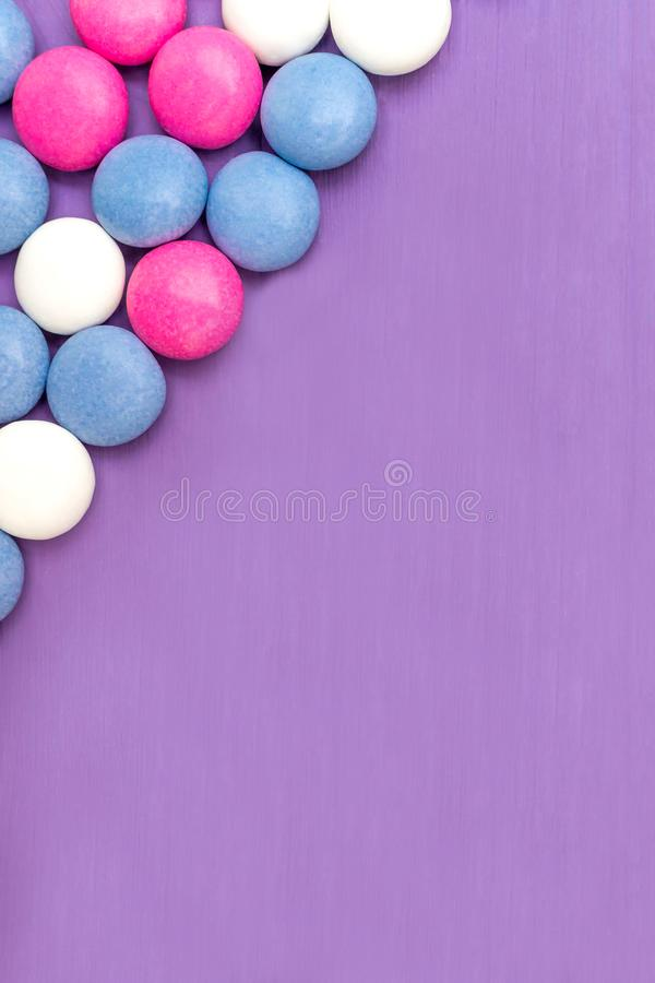 Upper left corner frame of colored chocolate coated candy. Top view of upper left corner frame of colored chocolate coated candy on wooden purple background royalty free stock photos