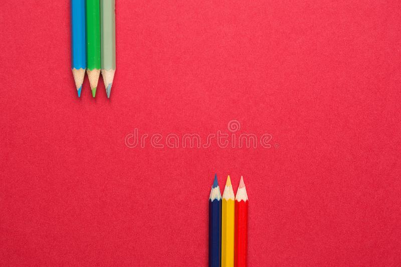 Upper and Lower Rows of Multicolored Pencils in Parallel Position Bottom and Top on Dark Red Paper Background. Business Creativity royalty free stock image