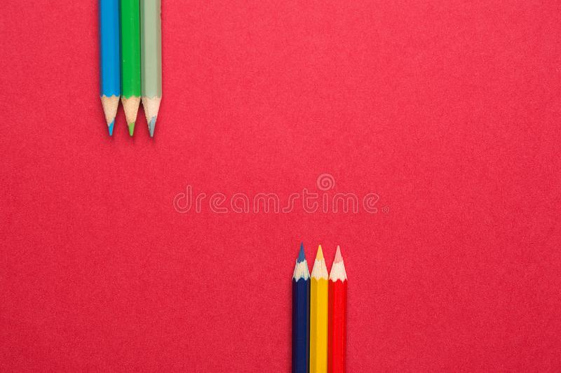 Upper and Lower Rows of Multicolored Pencils in Parallel Position Bottom and Top on Dark Red Paper Background. Business Creativity. Graphic Design Crafts Kids stock images
