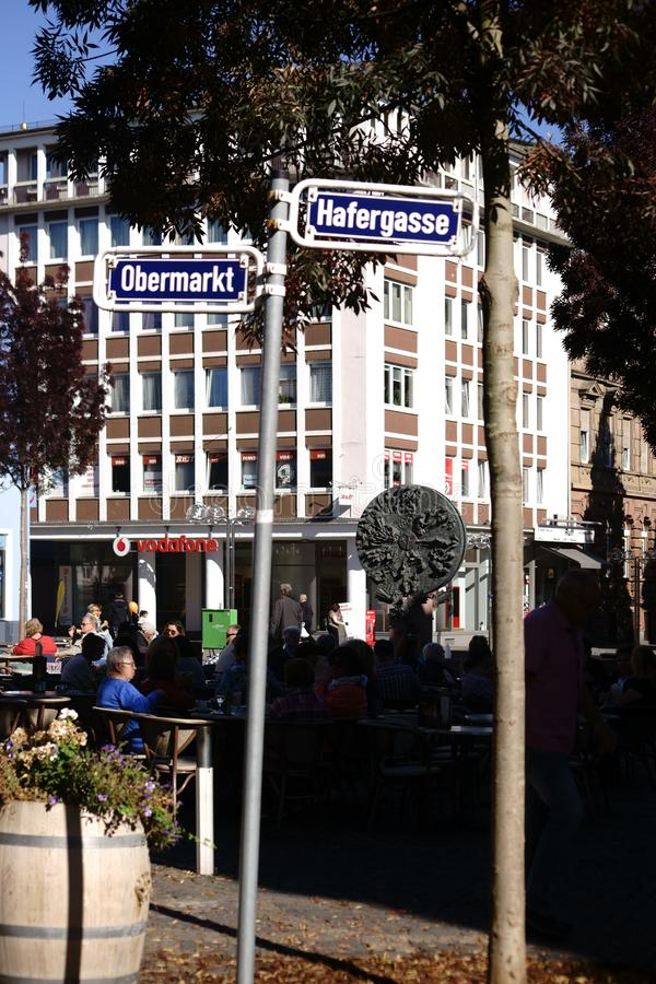 Upper market Worms. Worms, Germany - October 13, 2018: A well-visited cafe on the upper market behind street signs and in front of the Skulptur Schicksalsrad on stock photography