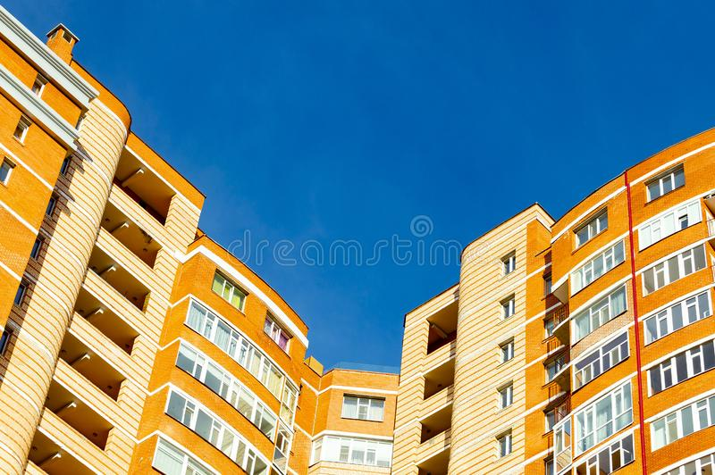 Upper part of the corner of an orange multi-story apartment building and blue sky. View from below royalty free stock photo