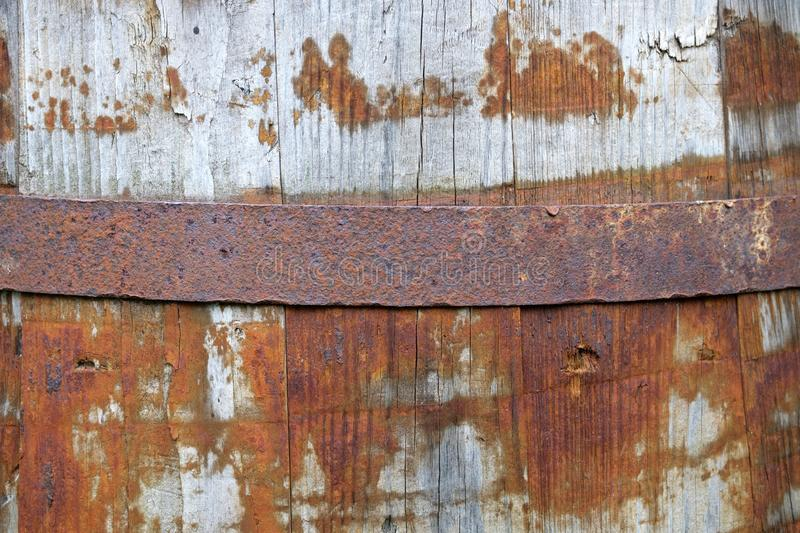 The upper part of an old wooden barrel on which an iron ring is put. Traces of rust on the tree stock photo