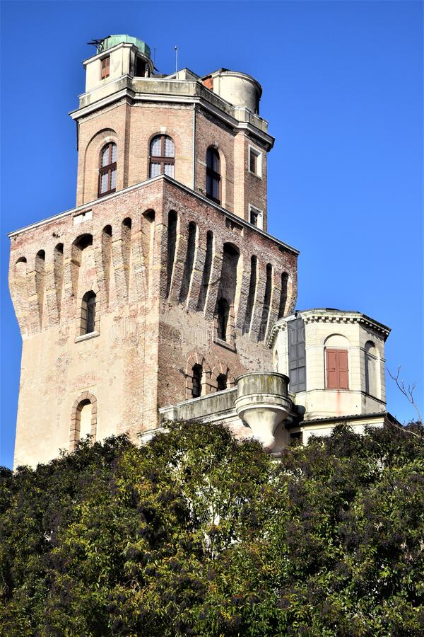 Upper part, protruding from the crowns of some trees and illuminated by the sun in the blue sky, of the Specola di Padova seat of. The ancient astronomical royalty free stock image