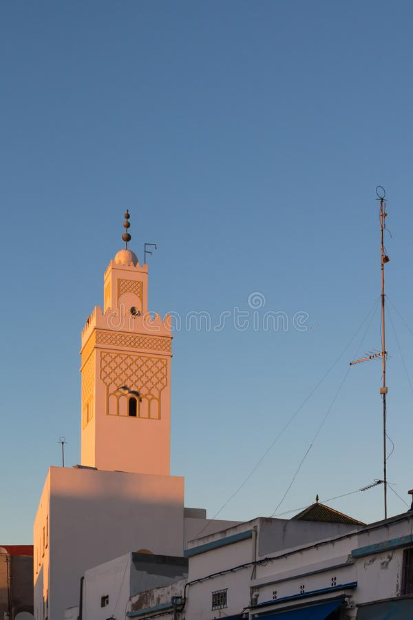 Tower of a mosque in Safi, Morocco. Upper part of a street with a tower of a mosque, enlighted by evening sunlight during sunset, creating an orange tone of the royalty free stock image