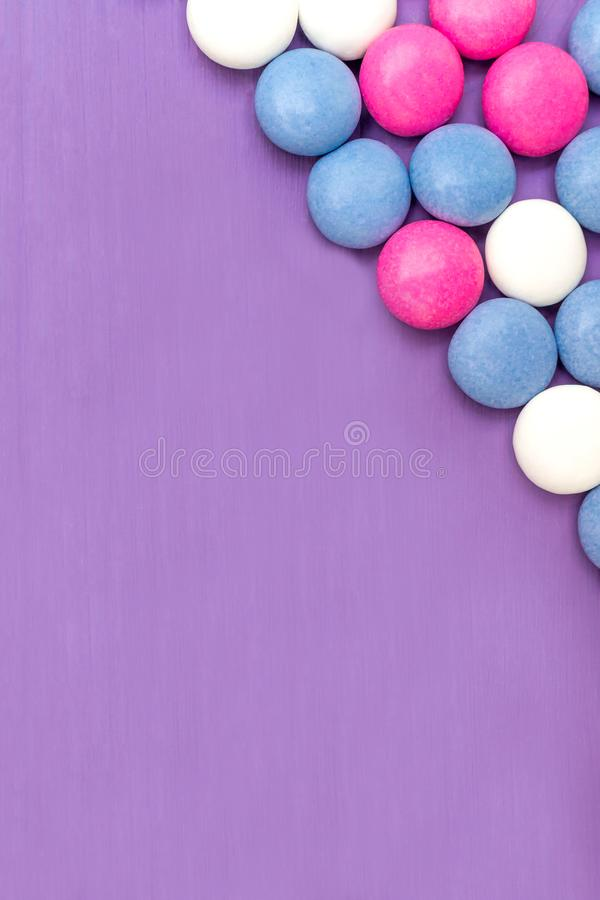 Upper right corner frame of colored chocolate coated candy. Top view of upper right corner frame of colored chocolate coated candy on wooden purple background royalty free stock photo