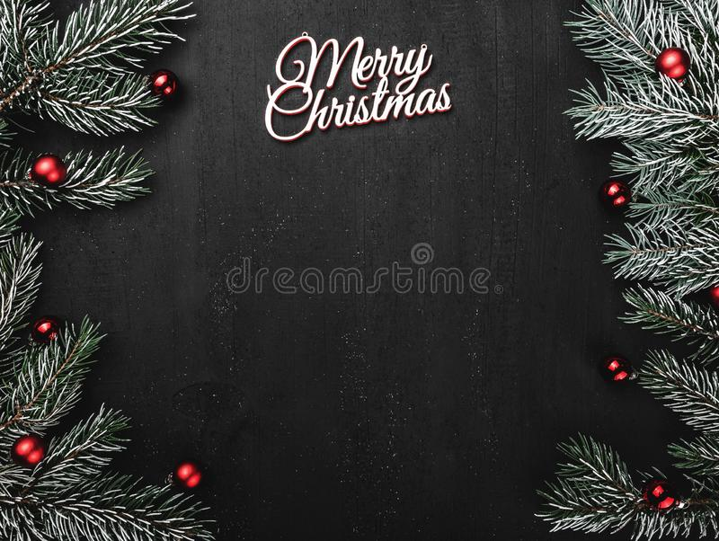Upper, top, view from above, evergreen branches, tree globes and white Merry Christmas inscription on black background. With space for text writing, greeting royalty free stock image