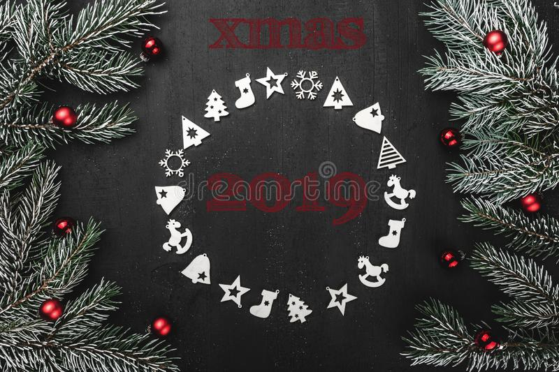 Upper, top, view from above, of handmade wooden toys circle, round shape, evergreen branches on black background. With the Christmas inscription 2019, greeting stock photos