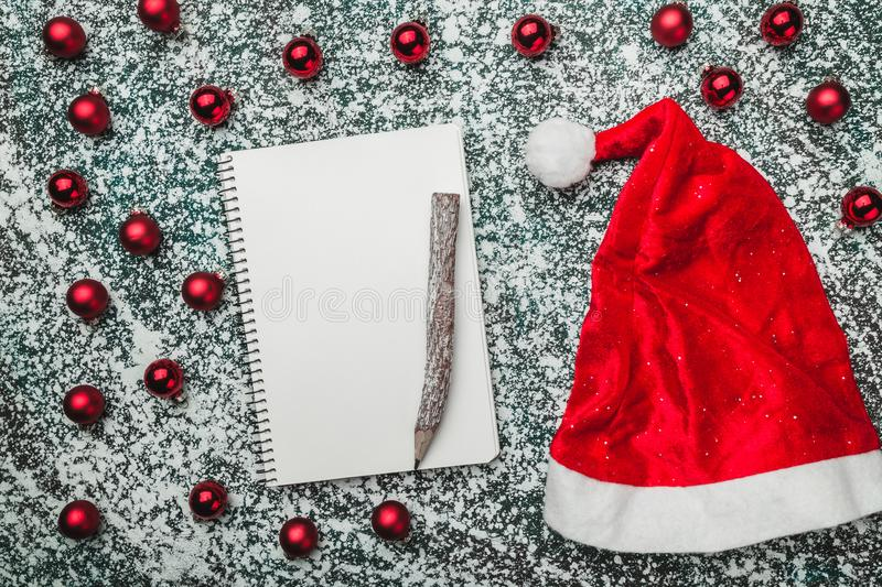 Upper, top, view from above of a notepad, wooden vintage pen, evergreen red toys, Santa hat on gray marble background royalty free stock photo