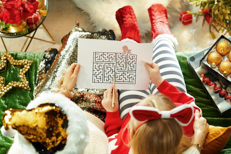 Elegant mother and child playing maze games. Upper view of elegant mother and child sitting on couch in the modern living room at Christmas playing maze games royalty free stock image
