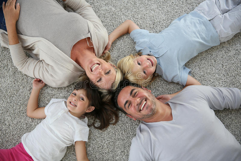 Upper view of family lying on the floor. Upper view of family of four laid on carpet royalty free stock photo