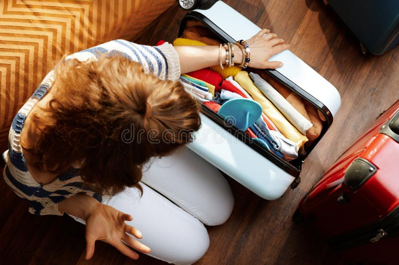 Furious modern woman closing over packed suitcase. Upper view of furious modern woman in white pants and striped blouse in the modern living room in sunny summer stock photo