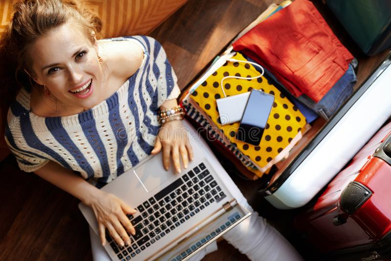 Woman in modern house in sunny summer day booking hotel online. Upper view of happy elegant woman in white pants and striped blouse in the modern house in sunny stock photos