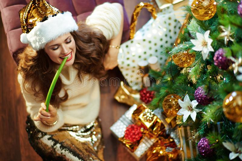 Happy modern 40 year old woman eating celery royalty free stock photo