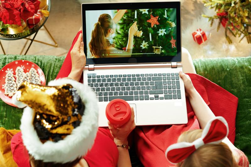 Modern mother and child watching Christmas movie on laptop royalty free stock image