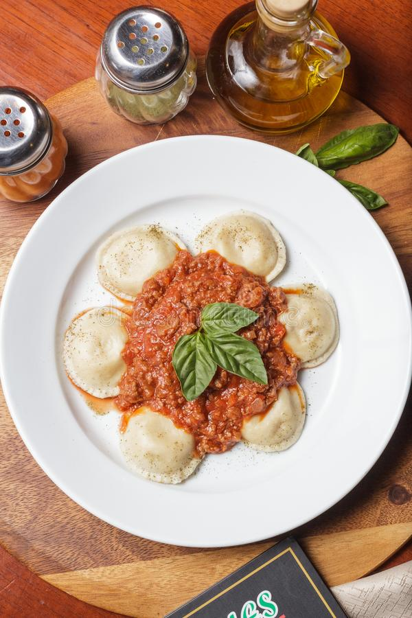 Upper view of a plate of sorrentinos. Stuffed pasta - with sauce, parmesan cheese, and decorated with some parsley´s leaves - Imagen stock images