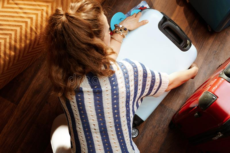 Stylish woman closing over packed suitcase. Upper view of stylish woman in white pants and striped blouse in the modern living room in sunny summer day closing royalty free stock photography
