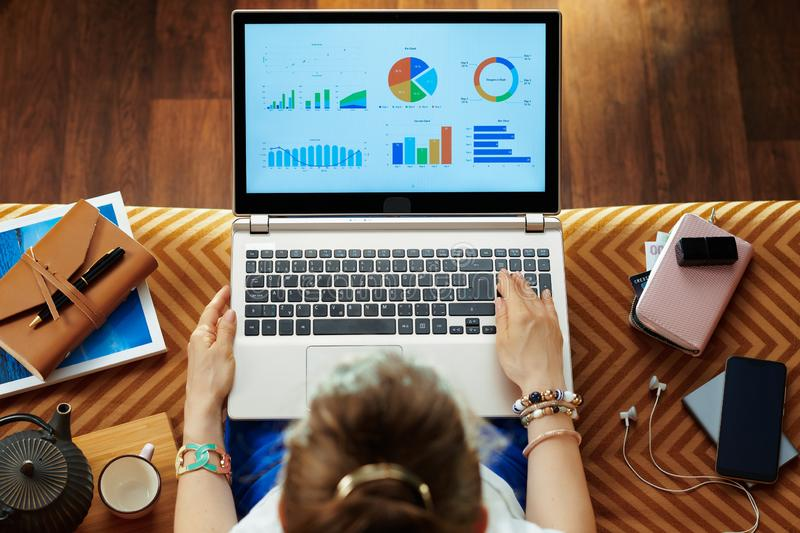Trendy woman looking at graphs on laptop screen. Upper view of trendy woman sitting on sofa in the modern living room looking at graphs on laptop screen royalty free stock image