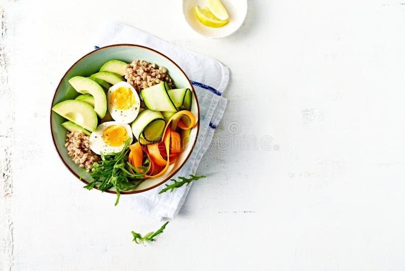 Uppföda bunken av grönsaker med ägget, avokadot och bovete arkivfoton