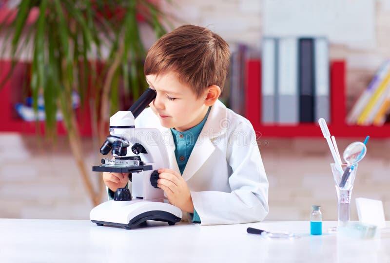 Uppföranden för ung unge experimenterar med mikroskopet i skolalabb arkivfoton