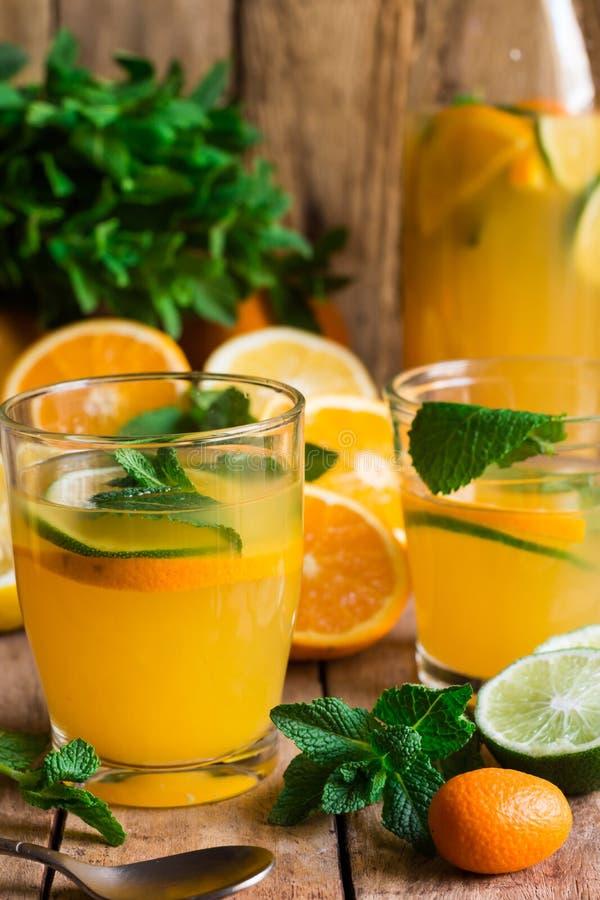 Uppfriskande citrus lemonad från den nya mintkaramellen för limefruktapelsiner i exponeringsglas och flaskan, skivade spridda fru fotografering för bildbyråer