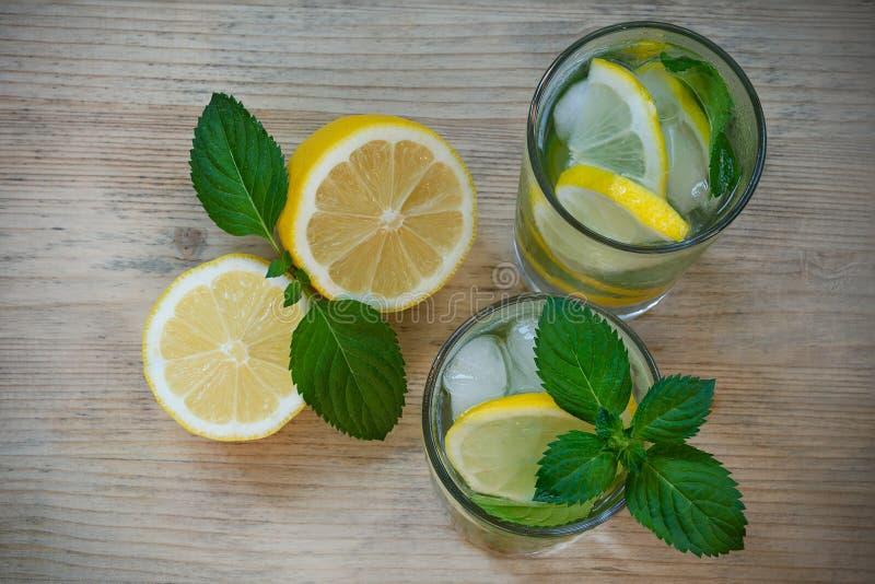 Uppfriskande drink med vatten, citron, mintkaramell, is i exponeringsglas på en träbakgrund Hemlagat detoxvatten arkivbild