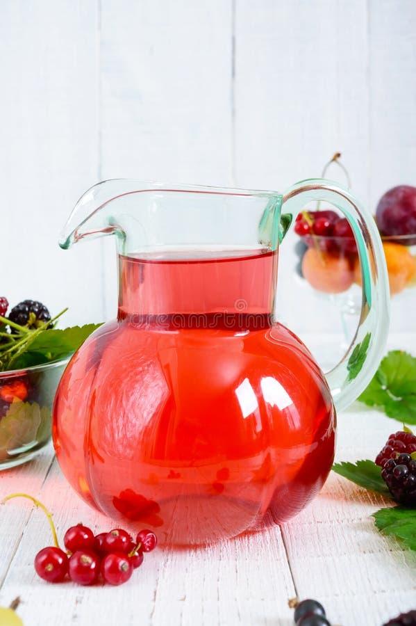 Uppfriskande drinkkompott av sommarbär i en glass krus royaltyfri fotografi