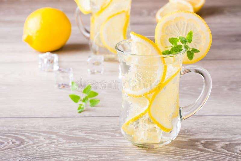 Uppfriskande kall mineralvatten med citron-, mintkaramell- och iskuber royaltyfri bild
