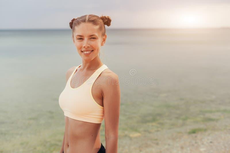 Uppfriskande lös genomkörare för havssida le den sunda konditionkvinnan i sportkugghjul på stranden som ser in i avståndet arkivfoton