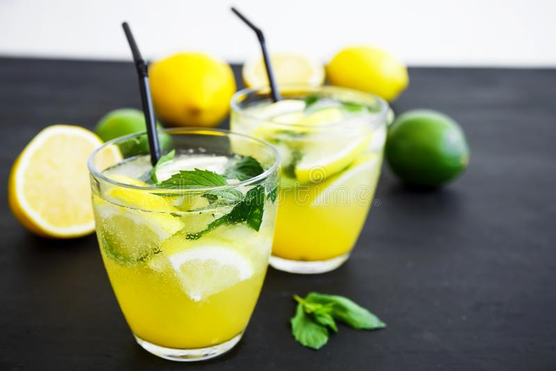 Uppfriskande lemonad i exponeringsglas med limefrukter, citroner och mintkaramellen Sommardrinkar arkivfoto