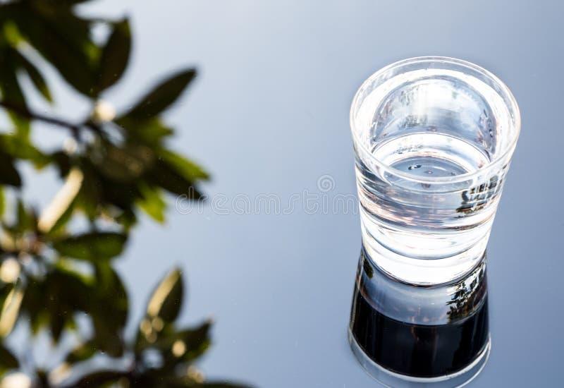 Uppfriskande vatten i genomskinligt exponeringsglas med reflexion mot bl arkivfoto