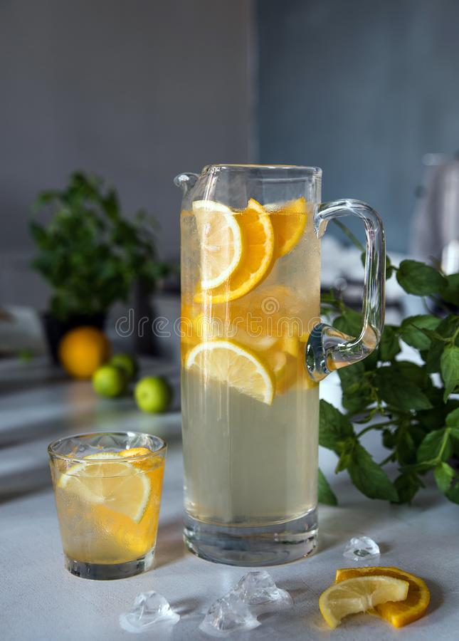 uppfriskningsommardrink Traditionell lemonad med citronen och orange mintkaramell och is på vit royaltyfri fotografi