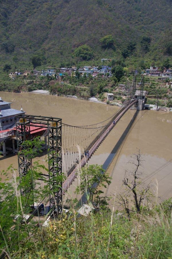 Upphängningbro i mitt av den Alaknanda floden, Indien fotografering för bildbyråer