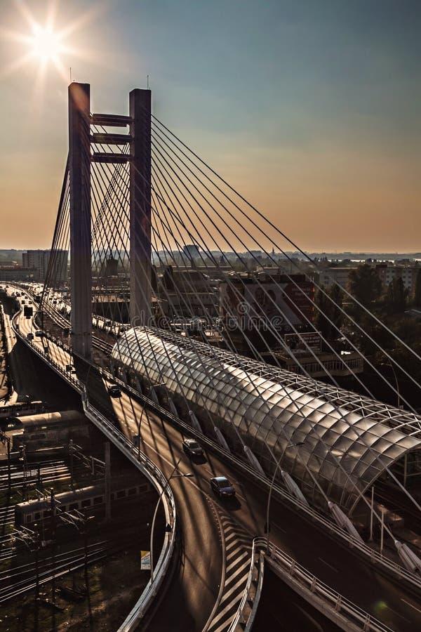 Upphängningbro på den stads- moderna gränsmärket för solnedgång royaltyfri foto