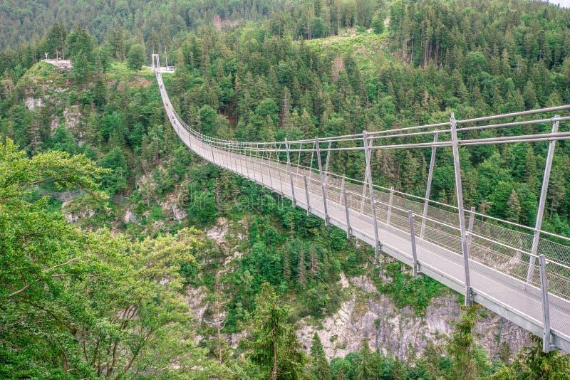 Upphängningbro på Reutte mellan två kullar i härligt landskaplandskap av fjällängar, Tirol, Österrike royaltyfri foto