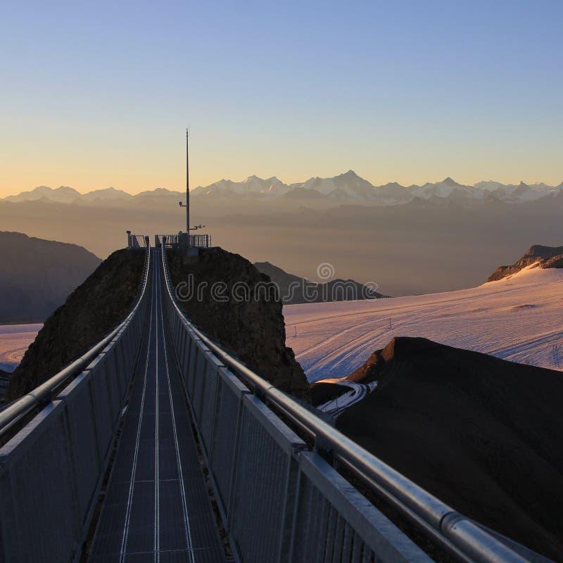 Upphängningbro som förbinder två bergmaxima Diablerets glaciär och avlägsen sikt av monteringen Weisshorn royaltyfria bilder