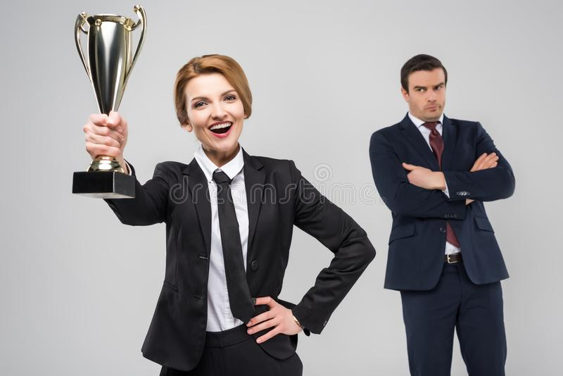 upphetsad affärskvinna med utmärkelse- och rubbningaffärsmannen bakom, arkivfoton