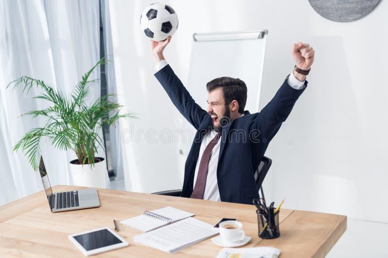 upphetsad affärsman i dräkt med fotbollbollen på arbetsplatsen royaltyfri foto