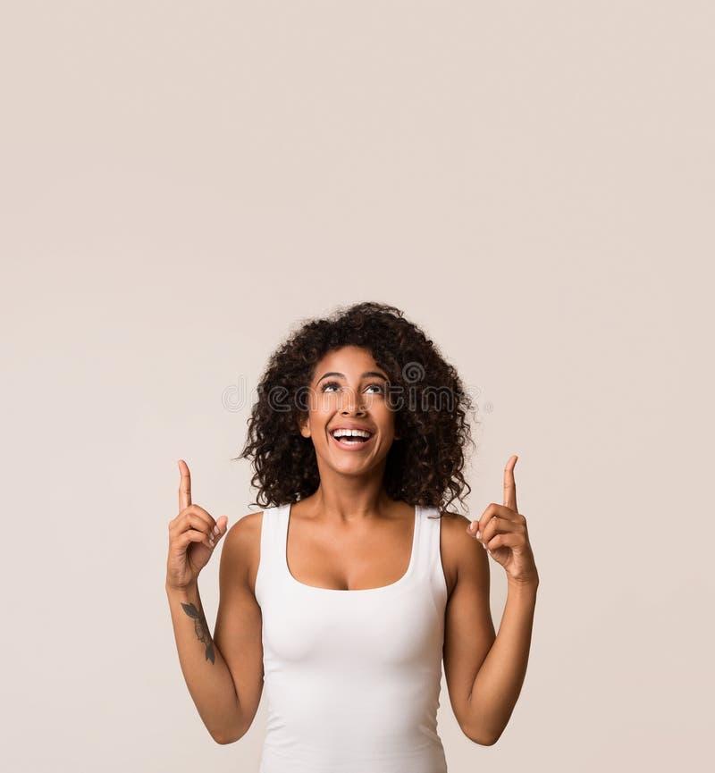 Upphetsad afrikansk amerikankvinna som pekar upp, kopieringsutrymme royaltyfria bilder