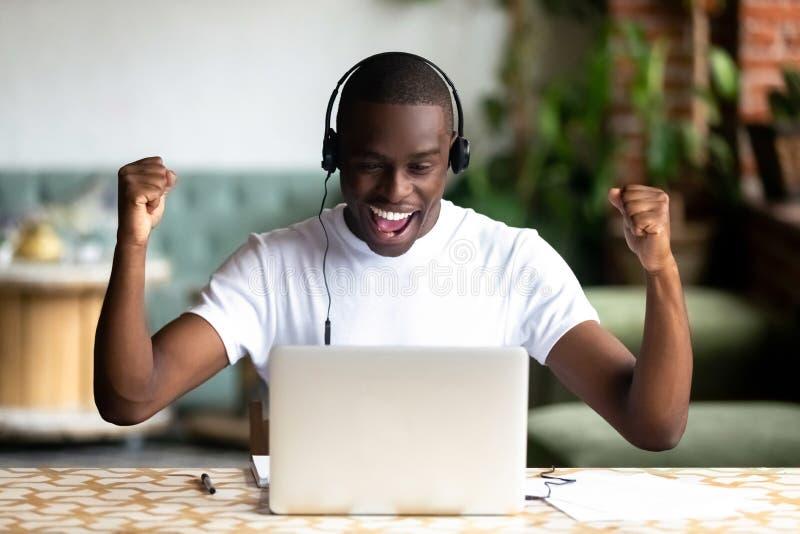 Upphetsad afrikansk amerikanman i hörlurar som firar framgång royaltyfri bild