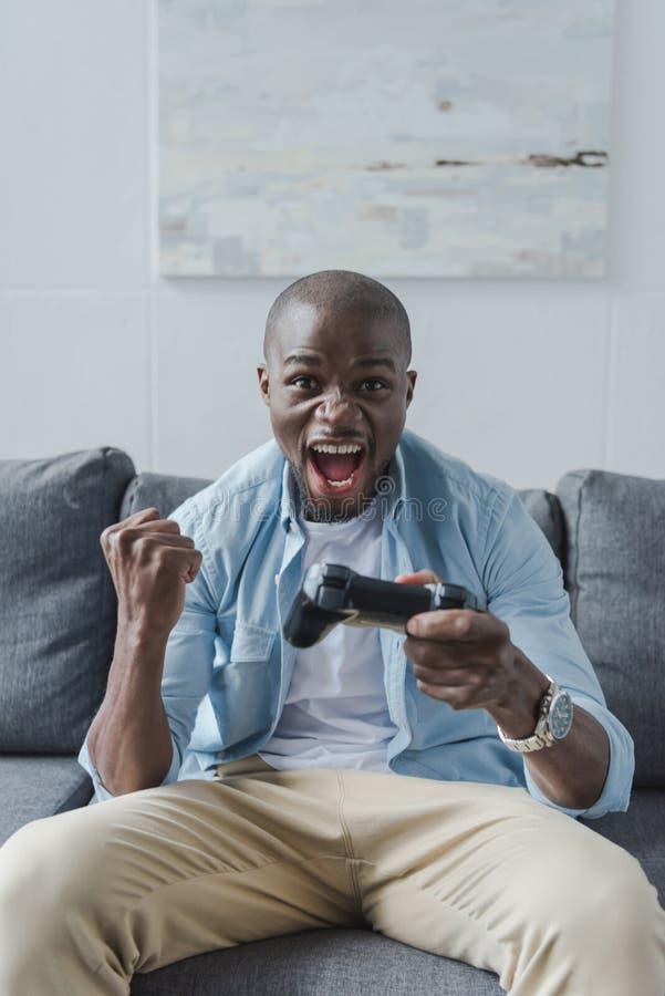 upphetsad afrikansk amerikanman som spelar videospelet med styrspaken royaltyfri bild
