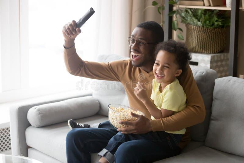 Upphetsad afrikansk fader med den hållande ögonen på fotbollleken för son på tv royaltyfria foton