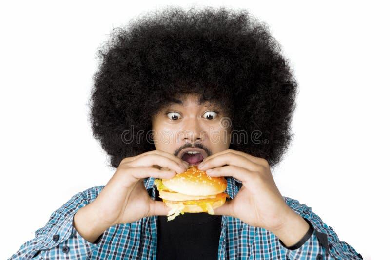 Upphetsad afro- man som äter en hamburgare arkivbilder