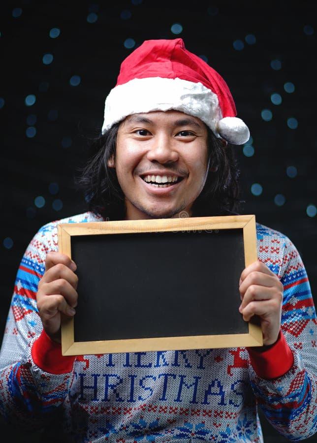 Upphetsad asiatisk man som bär Santa Hat och jultröjan Holdin arkivbilder
