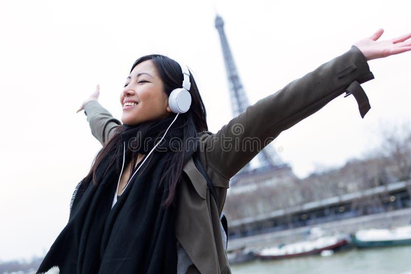 Upphetsad asiatisk ung kvinna som lyssnar till musik och framme tycker om ögonblick av Eiffeltorn i Paris arkivbild